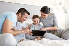 与片剂个人计算机的愉快的家庭在床上在家 免版税库存图片