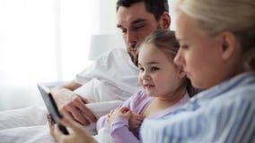 与片剂个人计算机的愉快的家庭在床上在家 股票视频