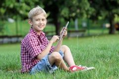 与片剂个人计算机的男孩戏剧在公园 免版税库存图片
