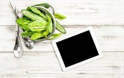 与片剂个人计算机的蔬菜沙拉菜在厨房用桌上 免版税库存照片