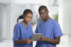 与片剂个人计算机的非洲pysician队在诊所 免版税图库摄影