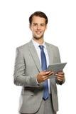与片剂个人计算机的年轻商人,微笑,当站立, isolat时 库存照片