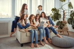 与片剂个人计算机计算机的孩子在社会网络沟通 小组十几岁的女孩使用小配件 库存图片
