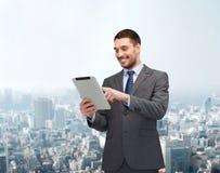 与片剂个人计算机计算机的微笑的buisnessman 免版税库存照片