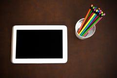 与片剂和五颜六色的铅笔的作家桌面标志 库存图片