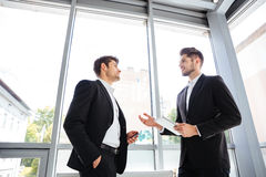 与片剂和手机的两个商人谈话在办公室 库存照片