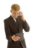 与片剂和移动电话的商人 免版税库存照片