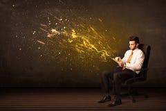 与片剂的商人和在背景的能量爆炸 免版税图库摄影