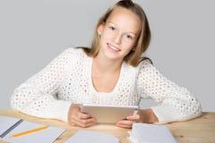与片剂的女孩读书 免版税库存图片