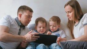 与片剂的家庭 看动画片的妈妈、爸爸和两个儿子孪生小孩说谎在床上的片剂 免版税图库摄影