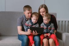 与片剂的家庭 看片剂的妈妈、爸爸和两儿子孪生坐在沙发 库存照片