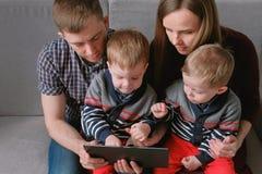 与片剂的家庭 看片剂的妈妈、爸爸和两儿子孪生坐在沙发 免版税库存图片