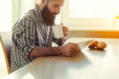 与片剂的微笑的人饮用的咖啡 免版税库存图片