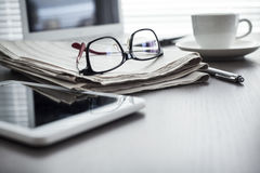 与片剂的报纸在桌上 免版税库存照片