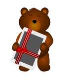 与片剂的玩具熊作为礼物 免版税库存图片