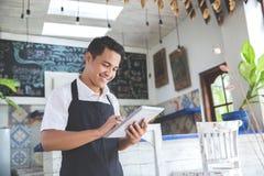与片剂的年轻男性咖啡馆所有者 免版税库存图片