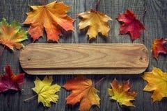 与牌,在老难看的东西木头的橙色叶子的秋天背景 免版税库存照片