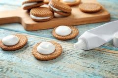 与牙膏的曲奇饼在桌上 免版税图库摄影