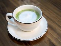 与牛奶泡沫杯子的热的matcha绿茶拿铁在咖啡馆的木桌上 从日本的时髦供给动力的茶趋向-健康饮料 免版税库存照片