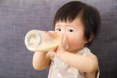 与牛奶瓶的亚洲女婴饲料 库存照片
