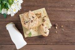 与牛奶瓶的被堆积的巧克力曲奇饼在木桌上 免版税库存照片
