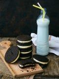 与牛奶白色蛋白软糖奶油和botle的自创巧克力曲奇饼在黑暗的背景的 选择聚焦 库存图片
