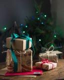 与牛皮纸包装的礼物和光的圣诞树 库存图片