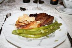 与牛肉、土豆焦干酪和芦笋内圆角的晚餐  免版税图库摄影