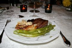 与牛肉、土豆焦干酪和芦笋内圆角的晚餐  免版税库存图片
