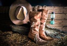 与牛仔帽和传统皮靴的静物画 免版税库存照片