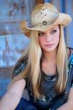 与牛仔帽和蓝眼睛的青少年的白肤金发的模型 免版税库存图片