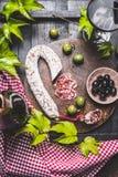 与特点的静物画意大利开胃小菜:蒜味咸腊肠、各种各样的橄榄、葡萄叶子和红葡萄酒在黑暗的木厨房用桌,上面上 免版税库存照片