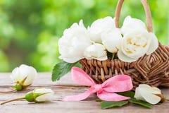 与狂放的玫瑰色花和桃红色丝带的土气柳条筐 图库摄影