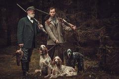 与狗和猎枪的两位猎人在传统射击衣物,摆在黑暗的森林背景 图库摄影