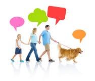 与狗和讲话泡影的家庭放松 库存图片