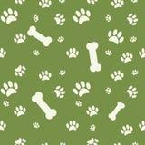 与狗爪子印刷品和骨头的背景在绿色 免版税库存照片