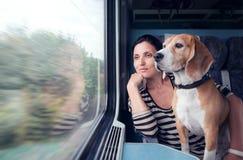 与狗的妇女旅行到火车无盖货车里 库存图片