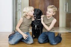 与狗的孩子在家 库存图片