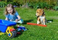 与狗的小女孩戏剧在庭院里 免版税库存图片