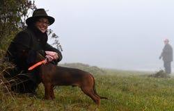 与狗的微笑的妇女猎人 免版税库存图片