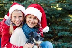 与狗的愉快的家庭在街道上的一棵圣诞树附近 免版税库存图片