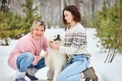与狗的母亲和女儿戏剧在冬天森林 免版税库存图片