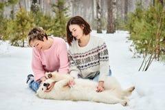 与狗的母亲和女儿戏剧在冬天森林 图库摄影