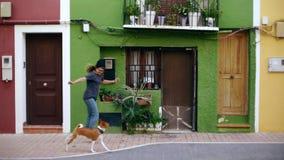与狗的滑稽的愉快的笑的妇女奔跑 股票录像