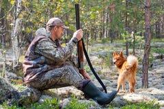 与狗的猎人在休息期间 库存图片