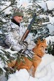 与狗的猎人在休息期间 库存照片