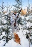 与狗的猎人在多雪的森林里 免版税库存图片