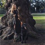 与狗的美好的女孩狩猎在森林里 免版税库存照片