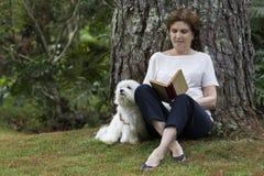读与狗的资深妇女一本书坐在她旁边 免版税库存图片