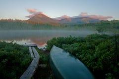 与独木舟的山和池塘场面 免版税库存照片